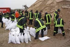 Die freiwilligen Feuerwehren beim Befüllen von Sandsäcken zur Wasserabwehr